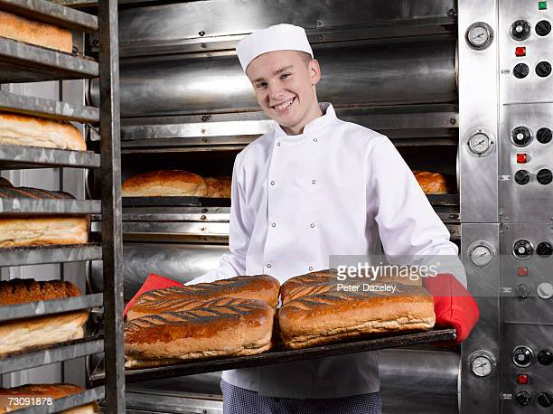 Teenage (16-17) baker presenting tray of fresh breads in bakery, portrait