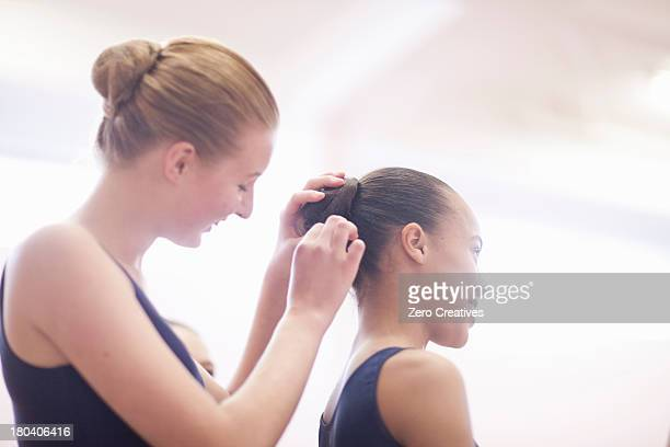 Teenage ballerina helping friend with hair