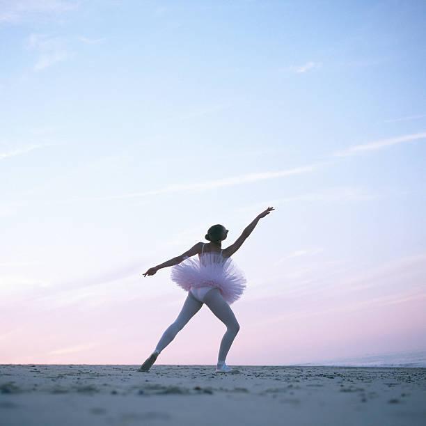 Teenage ballerina (16-18) performing on beach, rear view
