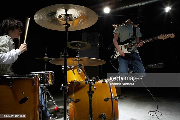teenage (14-16) band, boy playing drums, girl playing electric guitar - pop music stock pictures, royalty-free photos & images