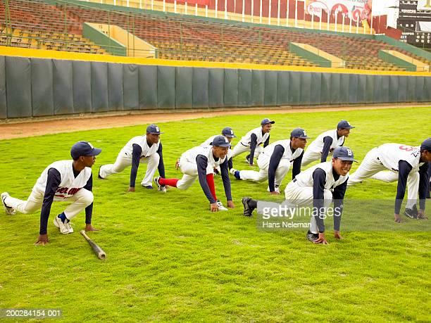 teenage baseball players (12-17) doing stretching exercise on field - hans neleman ストックフォトと画像