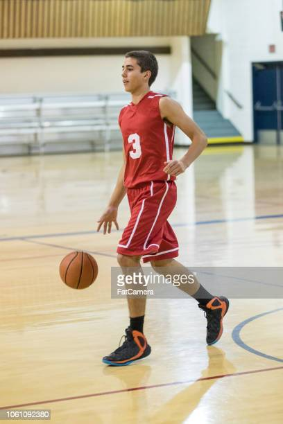 teenage basketball player dribbles down the court - charging sports stock pictures, royalty-free photos & images