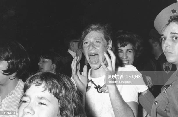 A teenage Beatle fan in hysterics as she catches a glimpse of her heroes