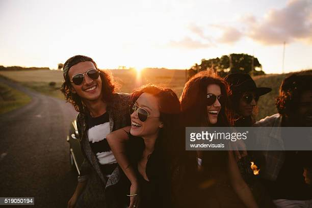 Teenage boho friends embraging and laughing at sunset