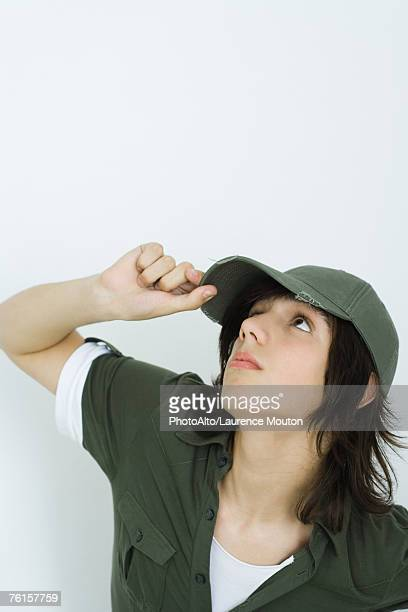 """""""teenage boy adjusting cap, looking up"""" - green hat stock pictures, royalty-free photos & images"""