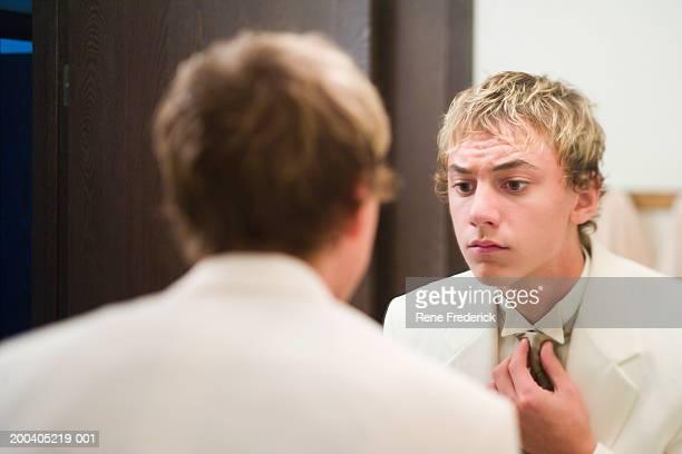 Teenage boy (14-16) adjusting tie in mirror