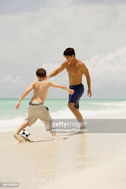 Teenage boy and a young man playing soccer on the beach