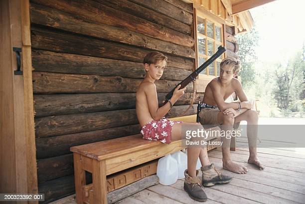 teenage boy (13-15) and boy (10-13) sitting on bench in porch, boy holding rifle - shirtless stock pictures, royalty-free photos & images