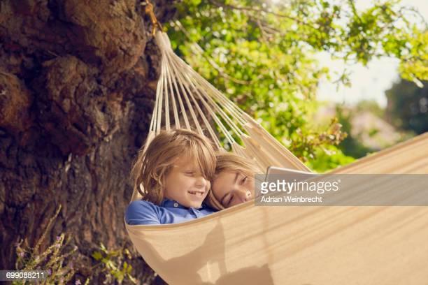 Teenage boy and brother reclining in garden hammock browsing digital tablet