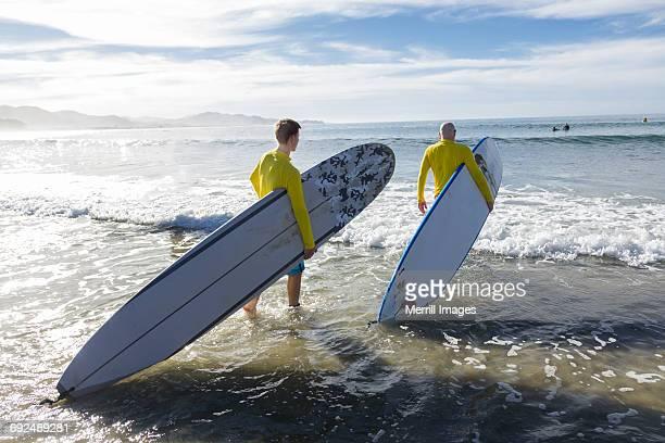 teenage boy and father surfing. - todos santos mexico fotografías e imágenes de stock