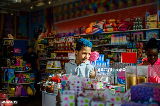 Teenage boy and girl browsing in candy shop, Brooklyn, USA