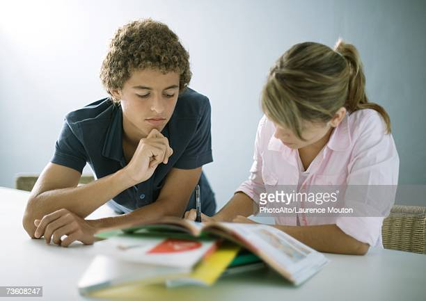 Teenage boy and girl doing homework together