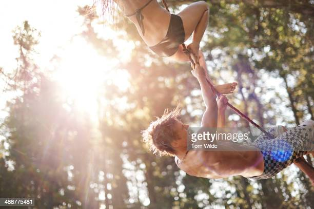 Teenage boy and girl hanging from a rope swing