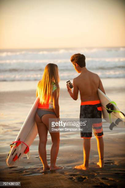 Teenage boy and girl holding surfboards texting on cell phone