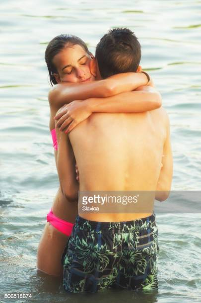 Teenage boy and girl hugging while standing in the summer sea