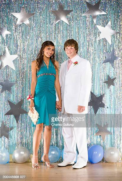Teenage boy and girl (14-16) in formalwear holding hands, portrait