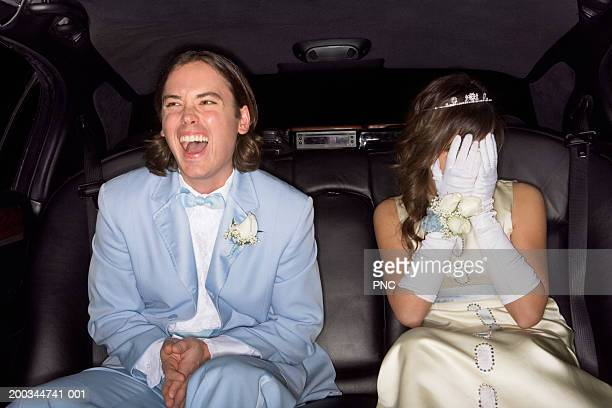 Teenage boy and girl (14-16) in formalwear laughing in limousine