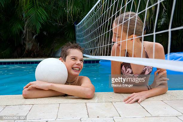 teenage boy (13-14) and girl (12-13) in swimming pool with volley ball and net - blasius erlinger stock pictures, royalty-free photos & images