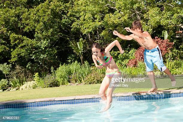 Teenager-Jungen und Mädchen springen in pool