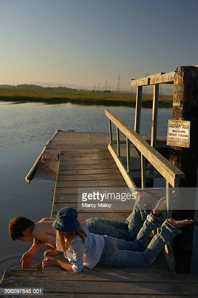 teenage boy and girl (17-19) lying on pier, looking in water - girl wear jeans and flip flops stock photos and pictures
