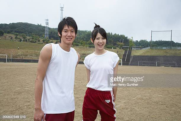 Teenage boy and girl (15-18) on athletic field, smiling, portrait