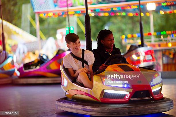 Teenage boy and girl on dodgems at funfair