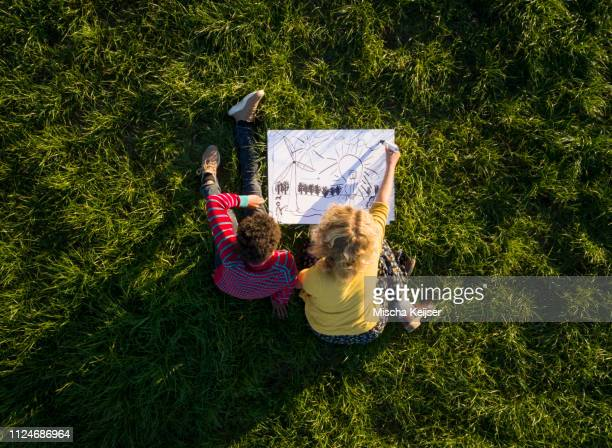 teenage boy and girl on grass experimenting and drawing sustainable energy solutions, overhead view - nachhaltigkeit stock-fotos und bilder