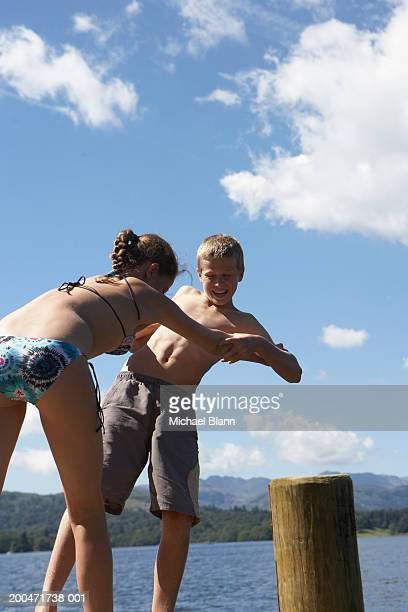 teenage boy and girl (12-14) play-fighting on jetty - female wrestling holds stockfoto's en -beelden