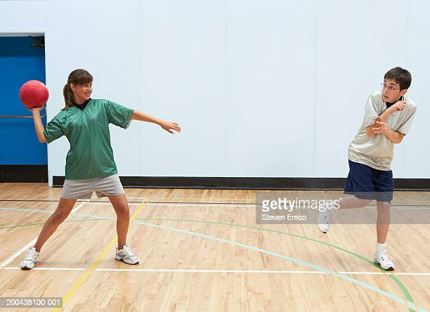 Teenage boy and girl (12-14) playing dodge ball in school gymnasium