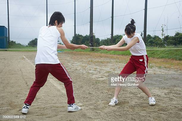 teenage boy and girl (15-18) playing tug-of-war on athletic field - rolled up pants stock pictures, royalty-free photos & images