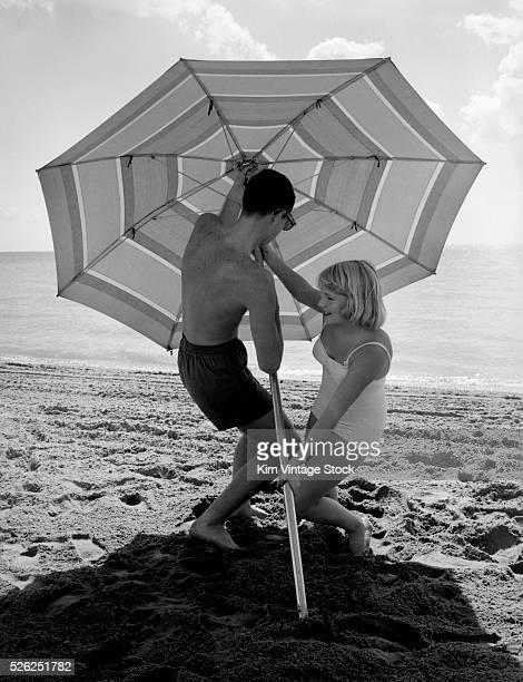 Teenage boy and girl put up umbrella on beach, ca. 1962.