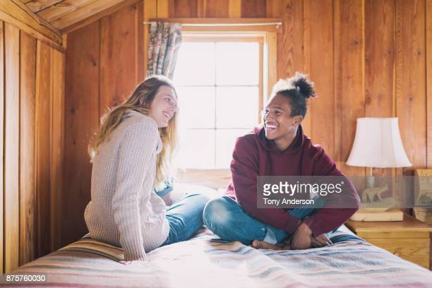 Teenage boy and girl sitting on bed in rustic cabin