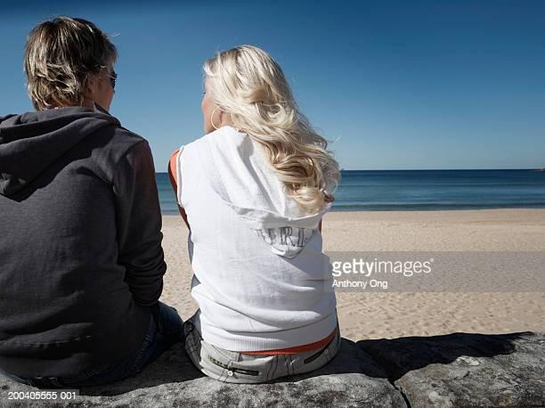 Teenage boy and girl (15-17) sitting on wall on beach, rear view
