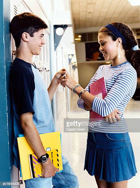 Teenage Boy and Girl Stand Face to Face By Lockers in a Secondary School Corridor, Flirting