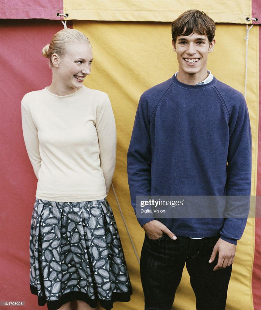 Teenage Boy and Girl Stand Side by Side in Front of a Fairground Tent, Laughing : Stockfoto