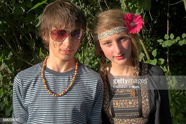 Teenage boy and girl twins dressed up as hippies for a fancy dress party UK