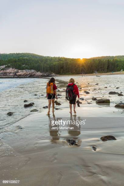 A teenage boy and girl walk on Sand Beach after a hike in Maines Acadia National Park.