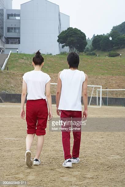 Teenage boy and girl (15-18) walking across athletic field, rear view