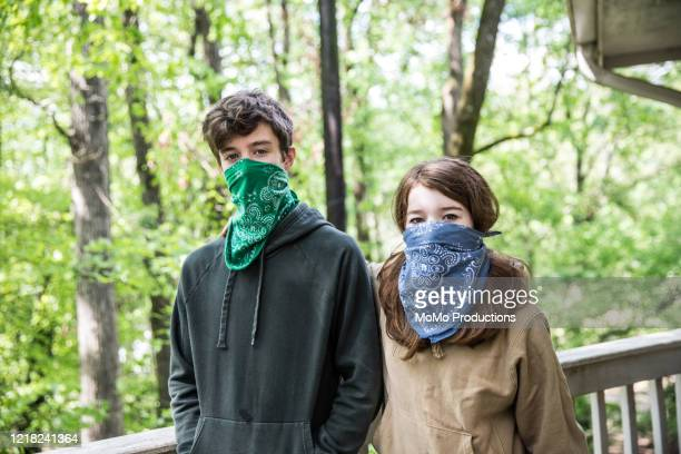 teenage boy and girl  wearing bandanas over faces - bandana stock pictures, royalty-free photos & images