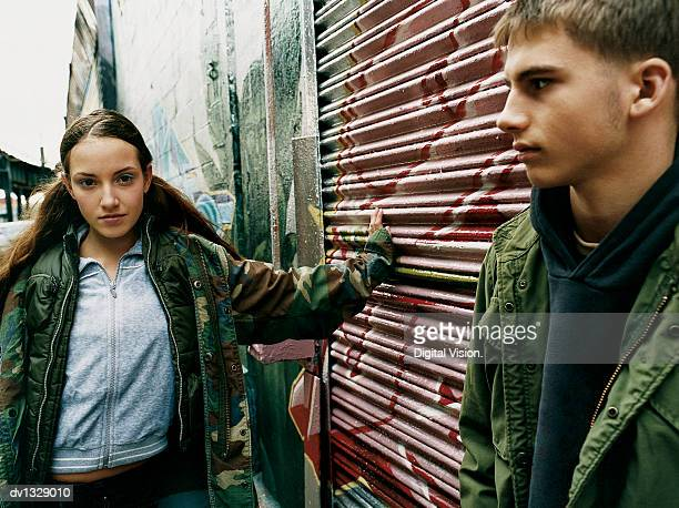 teenage boy and girl with attitude stand in an alley leaning on a roller shutters - chav stock photos and pictures