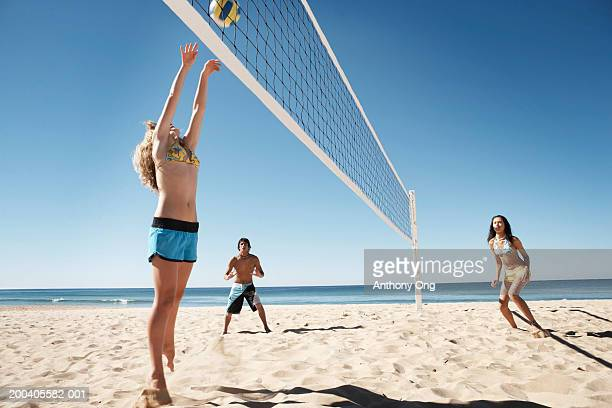 Teenage boy and girls (16-18) playing volley ball on beach