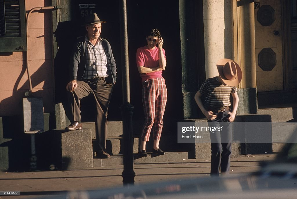 A teenage boy and his parents standing in a street in New Orleans. Colour Photography book.