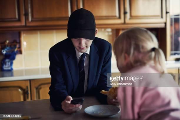 Teenage boy and his sister having breakfast