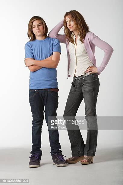 Teenage boy (13-14) and mid adult woman posing on white background