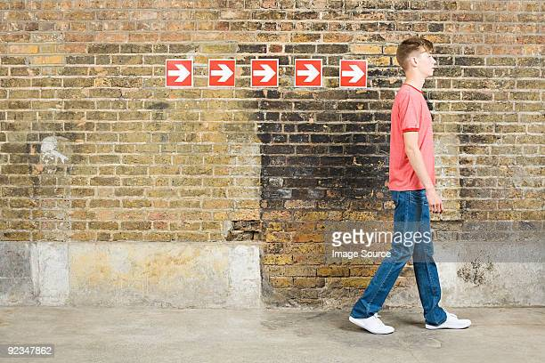 teenage boy and row of arrows - following arrows stock pictures, royalty-free photos & images