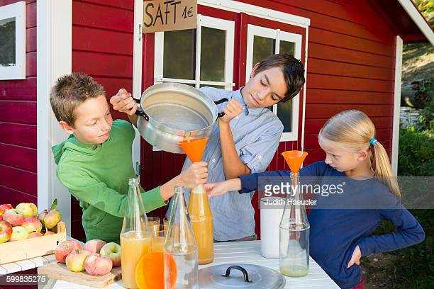 Teenage boy and siblings pouring fresh orange juice to sell at roadside