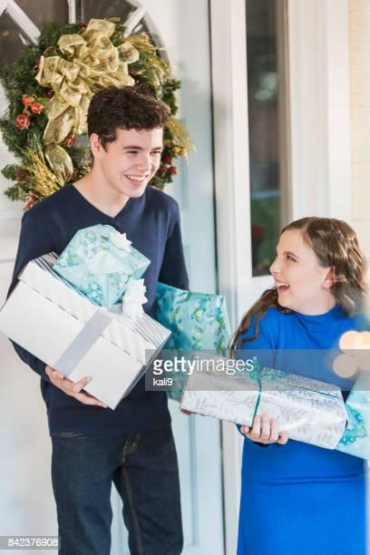 Teenage boy and sister carrying Christmas gifts
