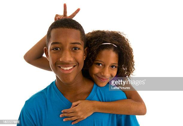 Teenage boy and sister embracing and gesturing bunny ears