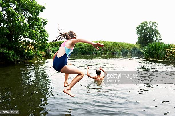 teenage boy and sister jumping into lake - lake stock pictures, royalty-free photos & images