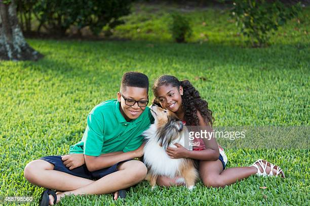 Teenage boy and sister petting their dog